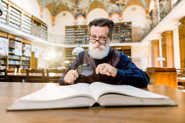 Oude man wetenschapper, bibliotheekmedewerker, het lezen van een boek in een bibliotheek, kijkend door het vergrootglas