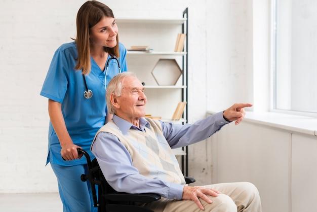 Oude man wijst naar het raam tijdens het praten met verpleegster