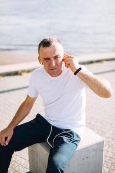 Oude man zijn oortelefoons in zijn oren stoppen