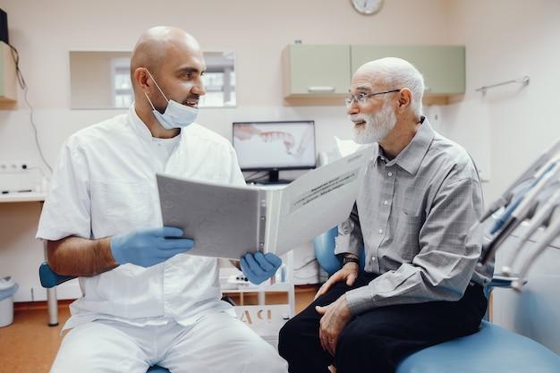 Oude man zit in het kantoor van de tandarts