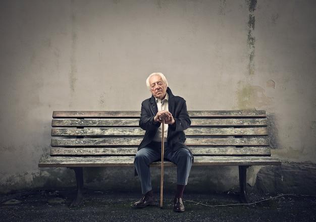Oude man zittend op een bankje