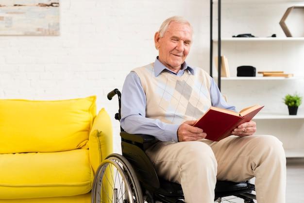 Oude man zittend op rolstoel tijdens het lezen van boek