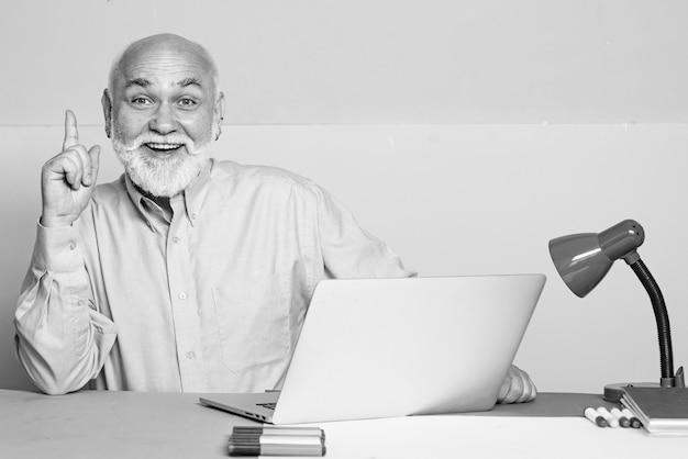 Oude manager met vriendelijk gesprek tijdens ontmoeting met laptop.