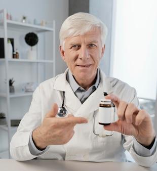 Oude mannelijke arts in zijn kantoor