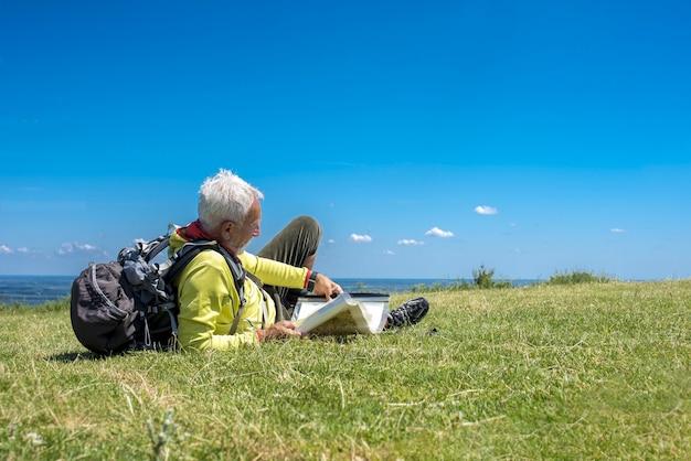 Oude mannelijke wandelaar die in een weide ligt en een kaart bekijkt
