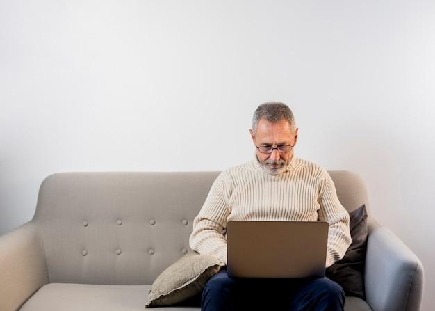 Oude mens die aan zijn laptop met exemplaar-ruimte werkt