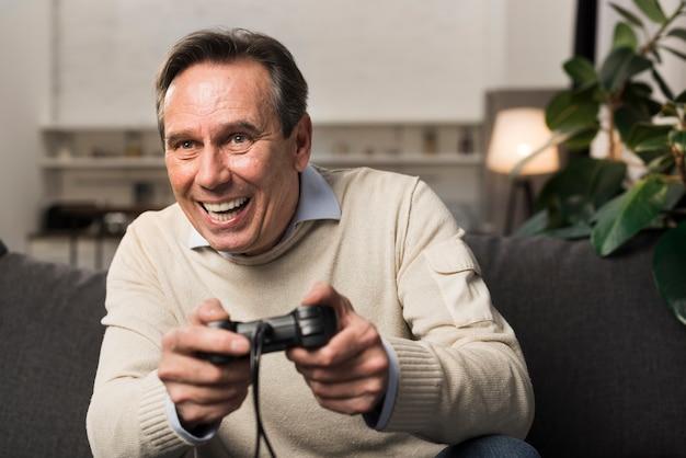 Oude mens die en videospelletje glimlacht speelt