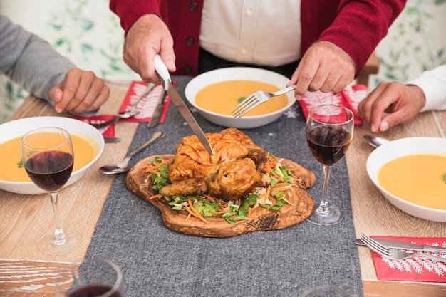 Oude mens die gebakken kip op feestelijke lijst snijdt