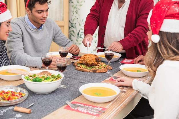 Oude mens die gebakken kip op kerstmislijst snijdt