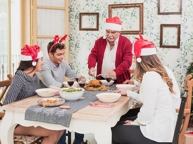 Oude mens die in kerstmanhoed gebakken kip op feestelijke lijst snijdt