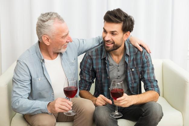 Oude mens die jonge het glimlachen kerel met glazen wijn op bank koestert