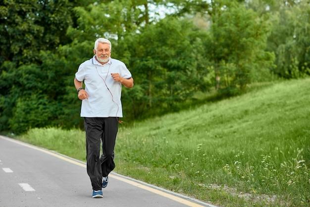 Oude mens die op de renbaan van het moderne stadspark loopt.