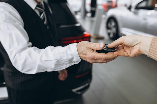 Oude mens die sleutels van auto in een autotoonzaal ontvangt
