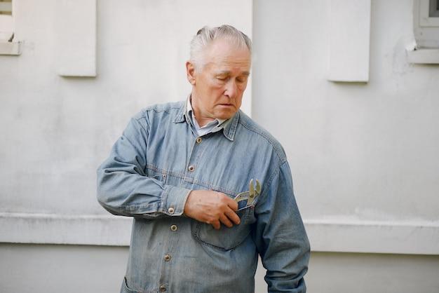 Oude mens die zich dichtbij de bouw met reparatiehulpmiddelen bevindt