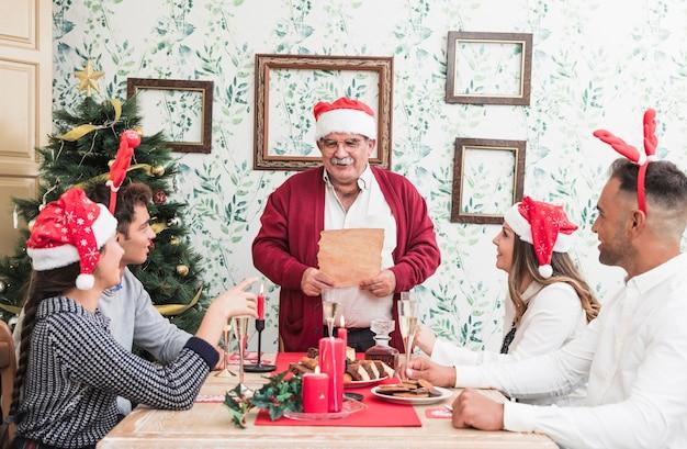 Oude mens die zich met document bij feestelijke lijst bevindt