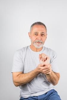 Oude mens die zijn handportret houdt