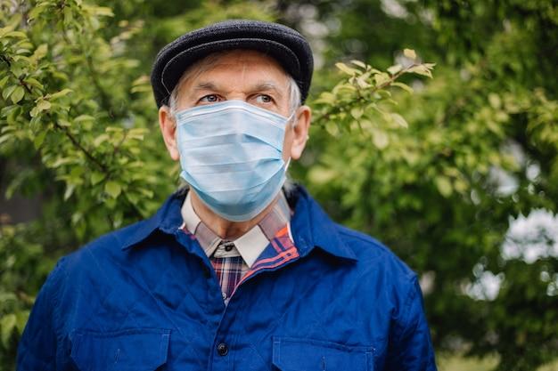 Oude mens in masker van de hoeden het beschermende geneeskunde in openlucht. grootvader met covid-bescherming op gezichten