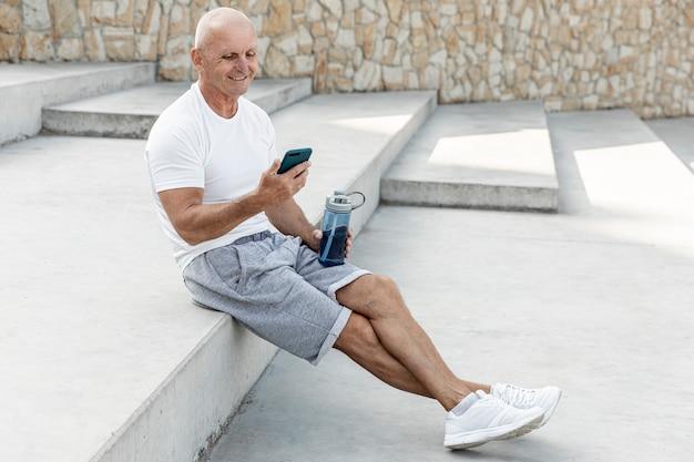 Oude mens rusten die zijn telefoon volledig schot bekijkt