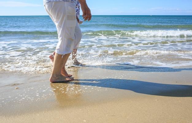 Oude mensen die een strandwandeling maken