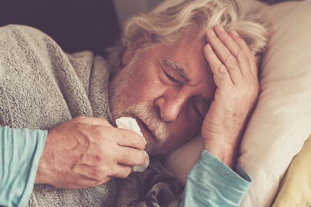 Oude mensen senior man met winter seizoensziekte koorts verkoudheidsproblemen die een apotheekmedicijn of hete thee drinken om gezond te worden
