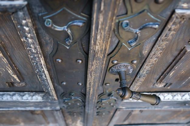 Oude metalen deurklink op de oude deur.