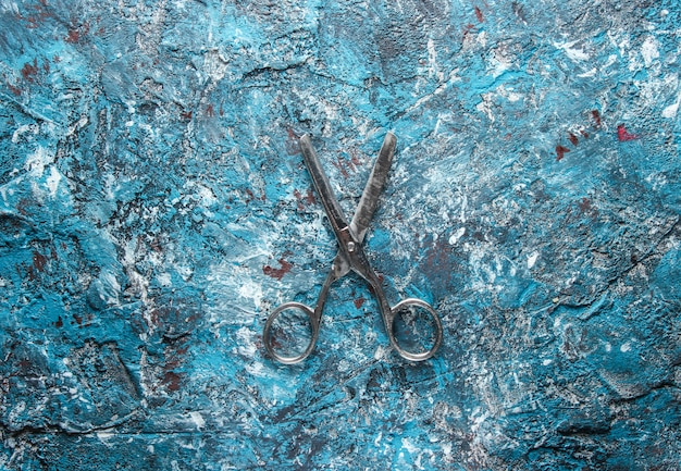 Oude metalen schaar op een blauwe betonnen ondergrond