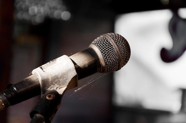 Oude microfoon op het podium verkwistend verlaten (selecteer focus)