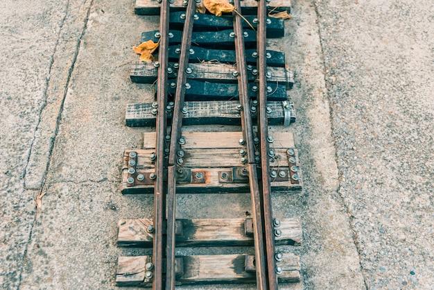 Oude miniatuur treinsporen bij zonsondergang.
