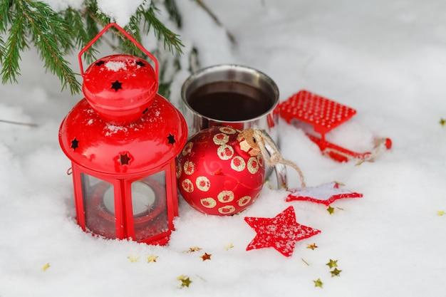 Oude mok met een warme drank en met een dennenappel in de sneeuw in de buitenlucht.