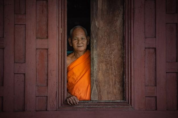 Oude monnik die zich bij venster bevindt