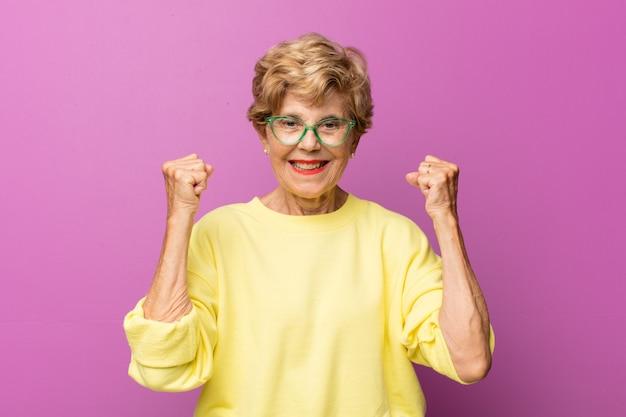 Oude mooie vrouw die zich blij, verrast en trots voelt, schreeuwt en succes viert met een grote glimlach