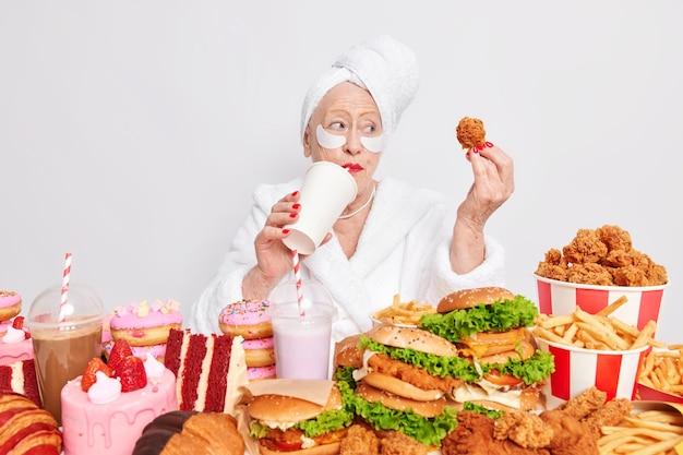 Oude mooie vrouw drinkt koolzuurhoudende drank houdt nuggets vast en consumeert te veel fastfood