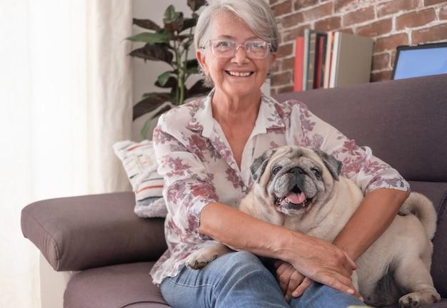Oude mopshond die thuis op de bank zit met een oudere vrouw die lacht en knuffelt