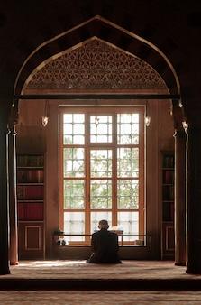 Oude moslim man bidden in de moskee bij het raam