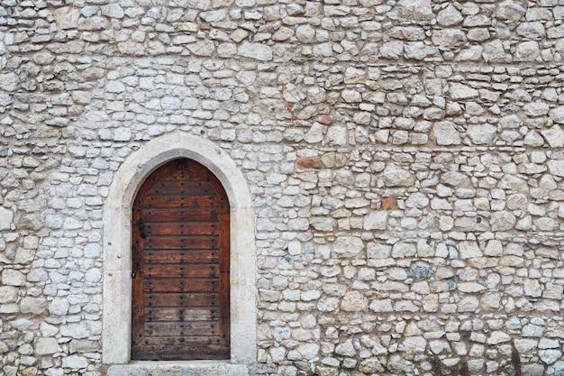 Oude muur en de voordeur in het middeleeuwse kasteel in krakau
