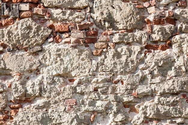 Oude muur gemaakt van grote stenen en gebroken bakstenen