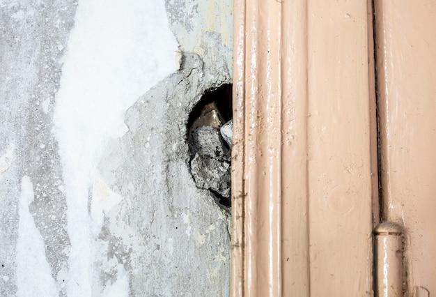 Oude muur in huis heeft renovatie nodig. beton bij de deur valt eruit. doe het zelf onderhoudswerkzaamheden. de flat repareren.
