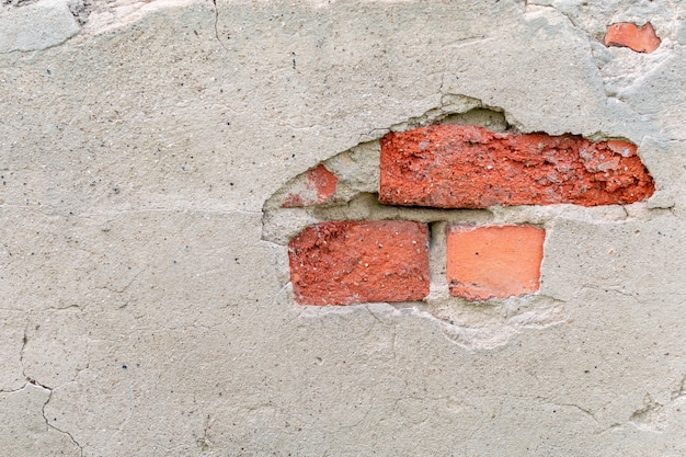 Oude muur met een gat van afgevallen gips en rood metselwerk. gebroken grijs cementoppervlak met scheuren. gevel van een oud industrieel gebouw.