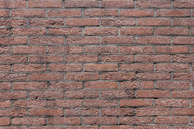 Oude muur van vele kleine rode bakstenen als achtergrond vooraanzicht close-up horizontaal