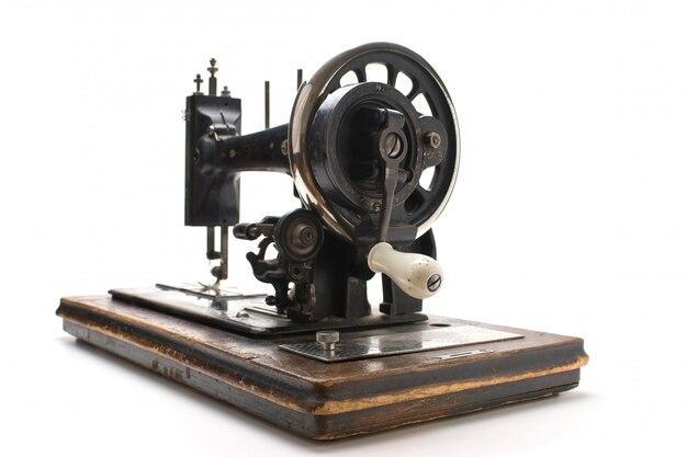 Oude naaimachine die op een witte oppervlakte wordt geïsoleerd