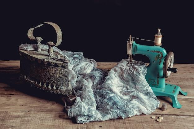 Oude naaimachine naast doek en ijzer