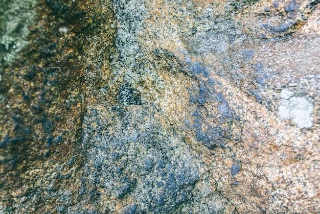 Oude natuurlijke grijze steentextuur met mosachtergrond.