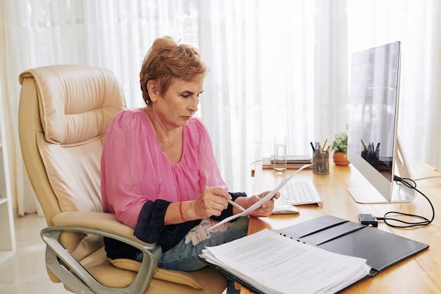 Oude onderneemster die contractdetails controleert