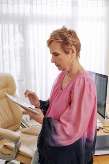 Oude ondernemer die aan tablet werkt