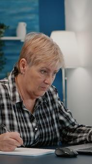 Oude ondernemer die een financieel project controleert van een bedrijf dat op een laptop kijkt die jaarlijkse statistische gegevens analyseert, aantekeningen maakt op een notebook die aan het bureau zit