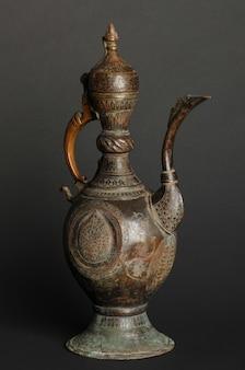 Oude oosterse metalen theepot op donkere achtergrond. antiek bronzen servies