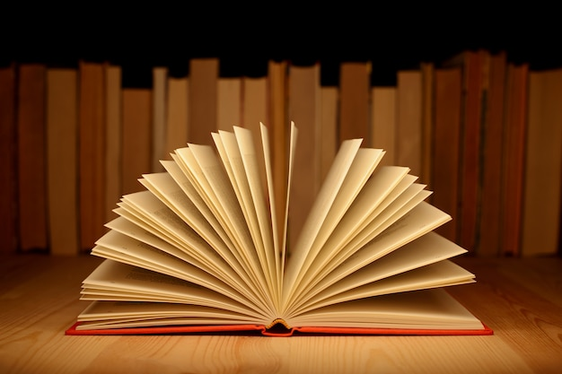 Oude open boek op houten tafel in de buurt van rij van vele oude en nieuwe boeken. concept van kennis, informatie.