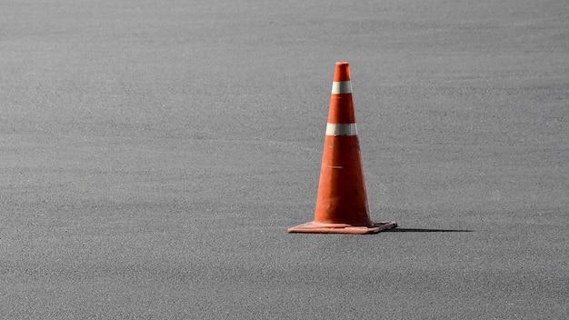 Oude oranje verkeerskegel op de asfaltweg