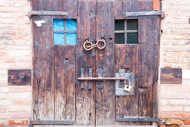 Oude oude houten dubbele deur met oude sloten en een handvat op de straten van bergamo, italië