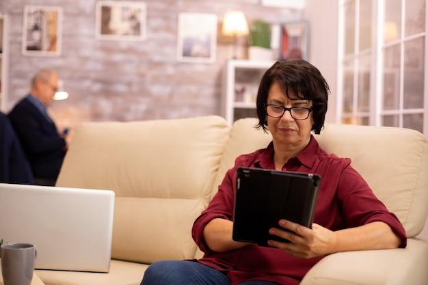 Oude oudere vrouw die op de bank zit en een digitale tablet-pc gebruikt in een gezellige woonkamer.